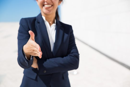 Smiling HR manager congratulating with getting job. Cropped portrait of positive woman in formal suit standing outdoors and offering hand for handshake. Business offer concept
